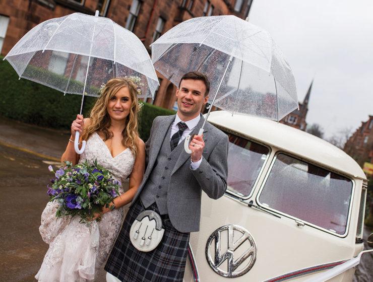 bride-and-groom-posing-under-umbrellas-in-the-rain