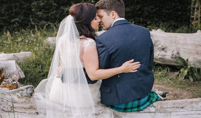 _bride-and-groom-kissing-on-log
