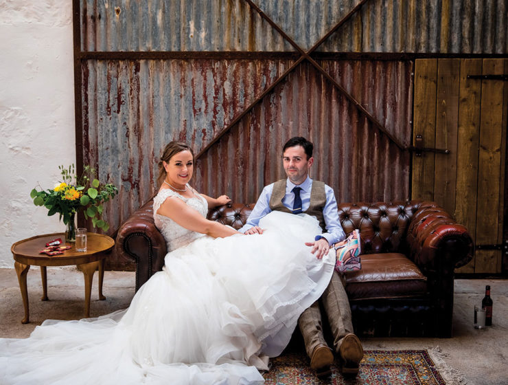bride-and-groom-sitting-on-leather-chesterfield-couch